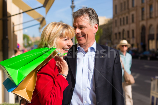 Mature couple strolling through city shopping in spring Stock photo © Kzenon
