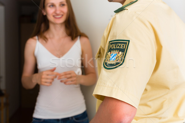 Police officer interrogation woman at front door Stock photo © Kzenon