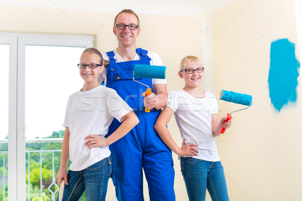 Father and Kids paint a wall in home Stock photo © Kzenon