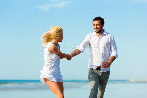 Couple on the beach running into glorious future Stock photo © Kzenon