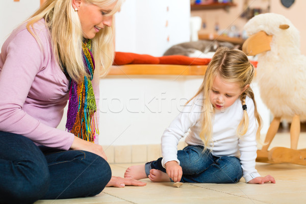 Girl playing with wooden toy spinner Stock photo © Kzenon