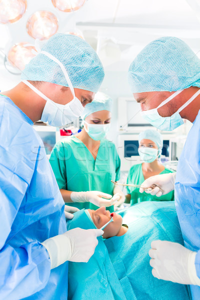 Surgeons operating in operation theater room Stock photo © Kzenon