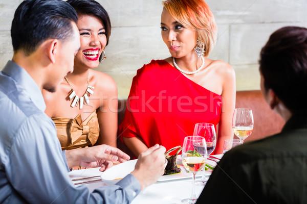 Asian friends dining in fancy restaurant Stock photo © Kzenon
