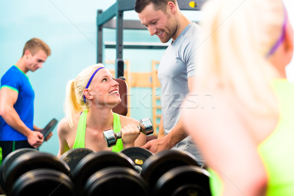 Woman in gym training with dumb bells Stock photo © Kzenon