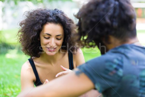 Latin couple on meadow with phone Stock photo © Kzenon