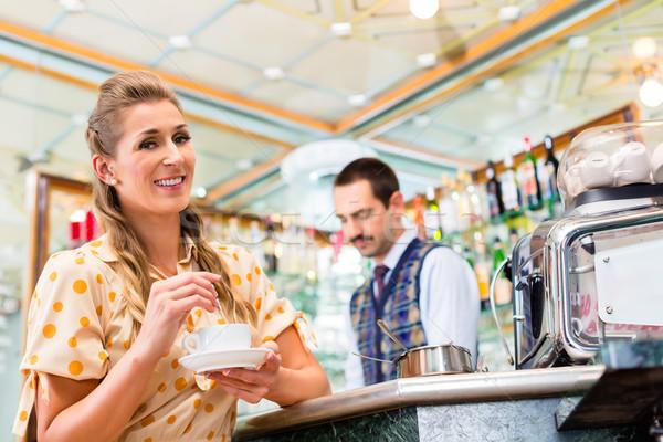 Girl in cafe or bar stirring in coffee cup, barista in back Stock photo © Kzenon