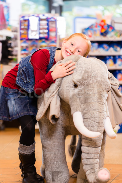 Little girl in toy store cuddling with stuffed animal Stock photo © Kzenon