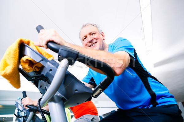 Senior doing sport on spinning bike in gym Stock photo © Kzenon