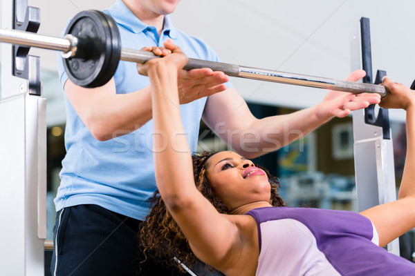 Black woman with Trainer lifting weights in gym for fitness Stock photo © Kzenon
