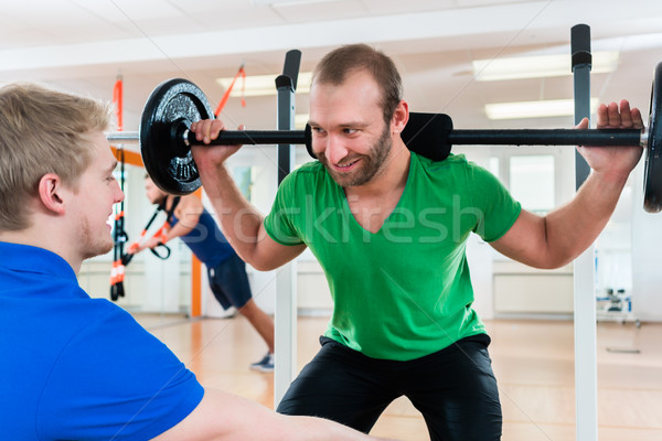 Athlete weightlifting in gym studio with his training partner Stock photo © Kzenon