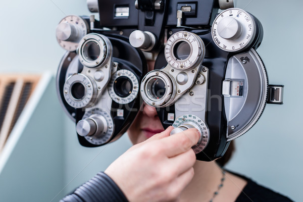 Woman at optometrist having eye sight testing Stock photo © Kzenon