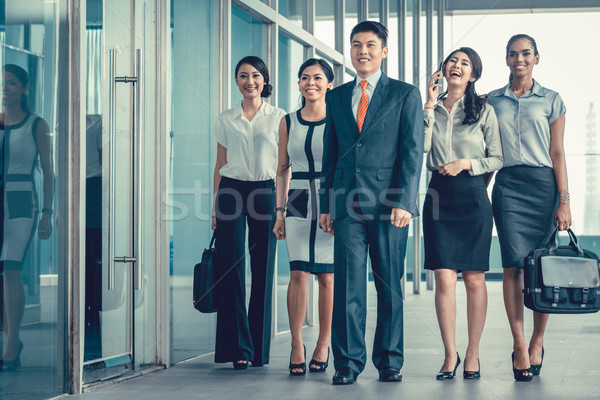 Asian business team of executives walking into office very deter Stock photo © Kzenon