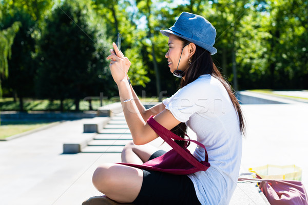 Stock photo: Young Asian woman making selfie pictures