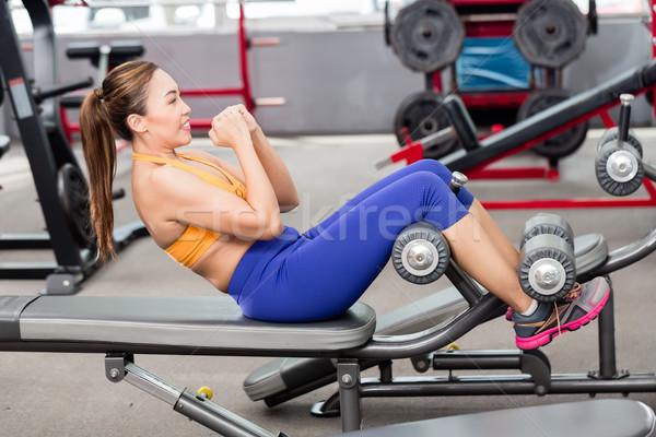 Asian woman doing sit-ups on bench in gym Stock photo © Kzenon