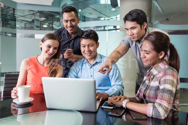 Több nemzetiségű csapat alkalmazottak néz vicces videó Stock fotó © Kzenon
