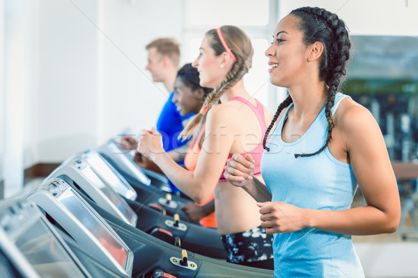 Side view of a fit happy woman and her training group on treadmill Stock photo © Kzenon
