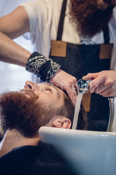Close-up of the hands of a skilled hairdresser giving a hair wash to customer Stock photo © Kzenon