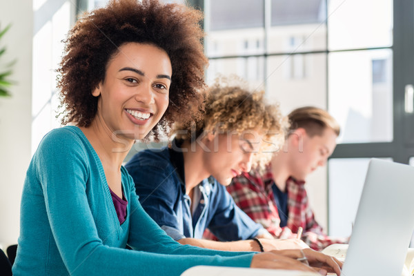 Stock photo: Portrait of a cheerful student sitting at desk in the classroom