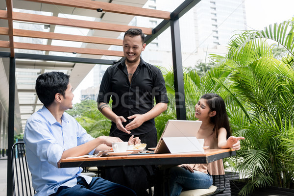 Friendly young waiter talking with the clients outdoors Stock photo © Kzenon