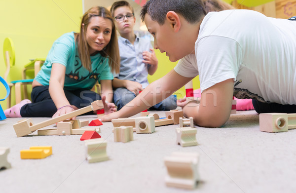 Female educator teaching children to build a train circuit Stock photo © Kzenon
