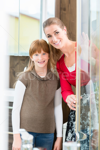 Cheerful woman with her daughter looking at a shower cabin Stock photo © Kzenon