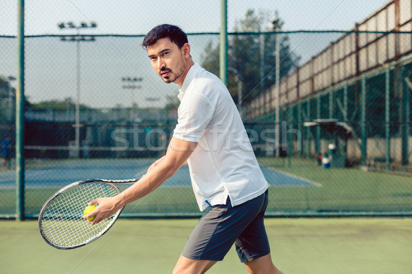 Determined tennis player looking forward with concentration before serving Stock photo © Kzenon