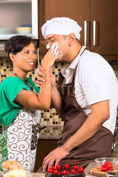 Asian couple baking chocolate cake in kitchen Stock photo © Kzenon