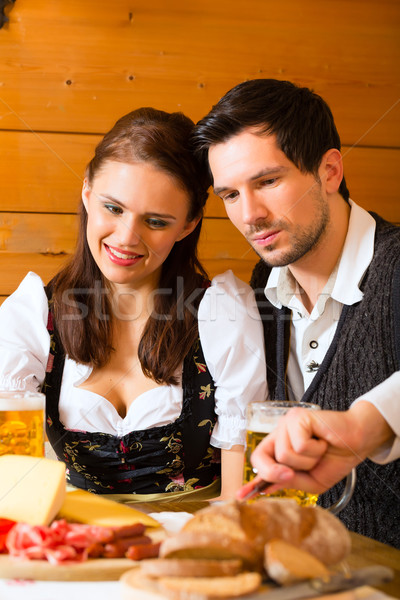 Young couple in a hunters cabin eating Stock photo © Kzenon
