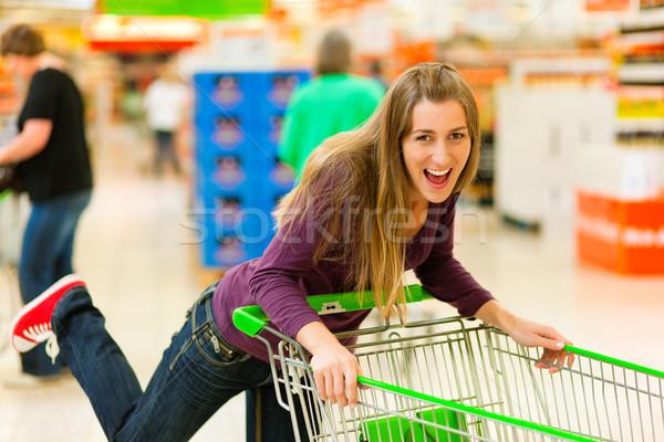 Woman in supermarket with shopping cart Stock photo © Kzenon