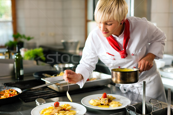 Female chef in a restaurant or hotel kitchen cooking Stock photo © Kzenon