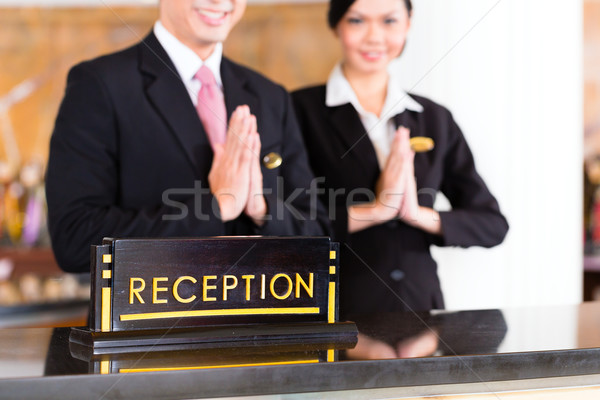 Chinese Asian reception team at hotel front desk Stock photo © Kzenon