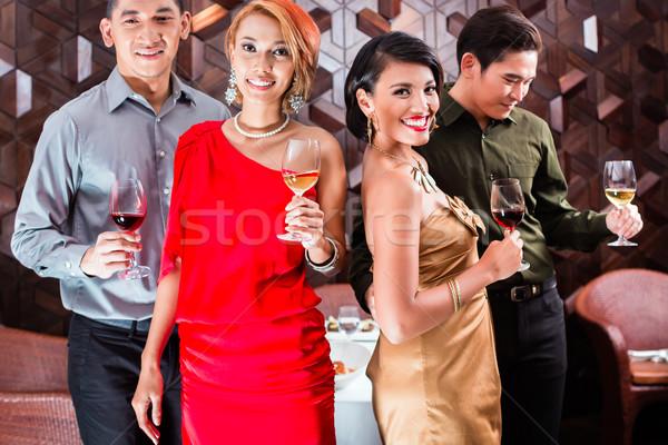 Asian friends drinking wine in fancy bar Stock photo © Kzenon