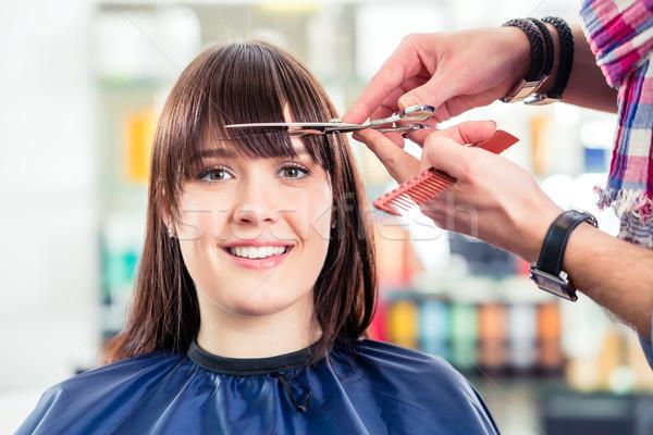 Hairdresser cutting woman bangs hair in shop Stock photo © Kzenon