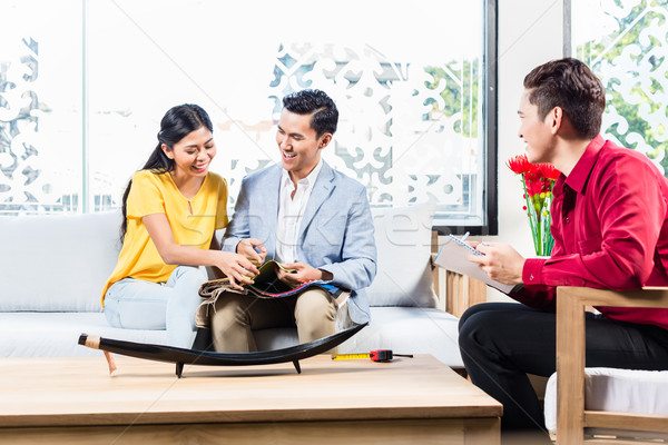 Stock photo: Couple with shop assistant in furniture store