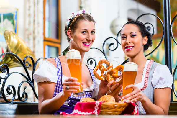 Girlfriends with Pretzel and Beer in Bavarian Inn Stock photo © Kzenon