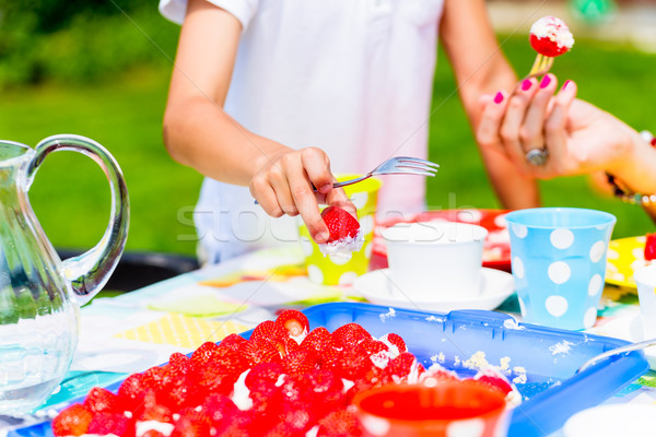 Girls cutting piece of strawberry cake in garden Stock photo © Kzenon