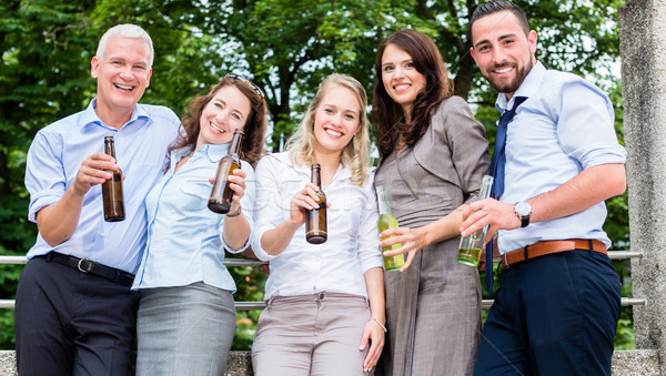 Office colleagues drinking beer after work Stock photo © Kzenon