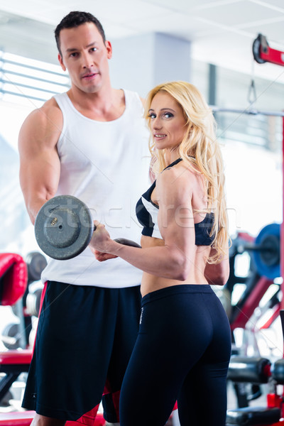 Woman in gym with barbell assisted by fitness trainer Stock photo © Kzenon