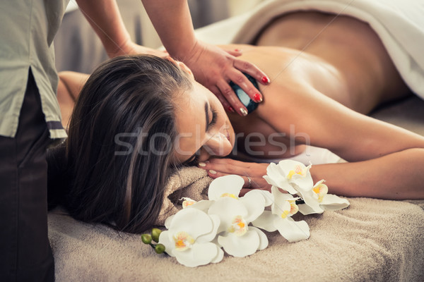 Stock photo: Woman enjoying the therapeutic effects of a traditional hot ston