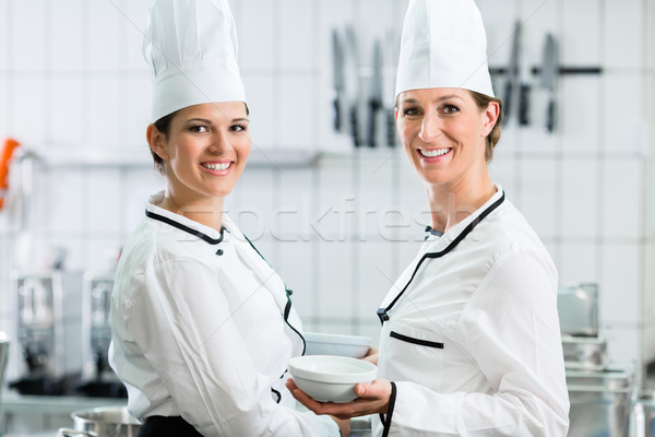 female chefs in commercial kitchen wearing white uniforms Stock photo © Kzenon