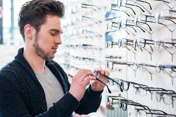 Człowiek półka okulary optyk sklep patrząc Zdjęcia stock © Kzenon