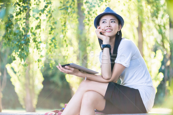 Asian woman using a tablet PC outdoors Stock photo © Kzenon
