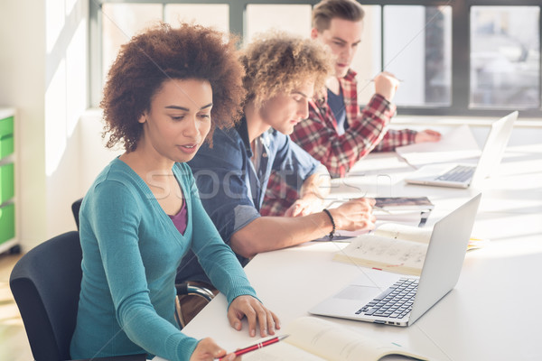 Portrait of a cheerful student sitting at desk in the classroom  Stock photo © Kzenon