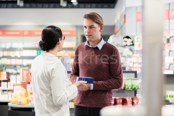 Experienced pharmacist checking the indications of a medicine Stock photo © Kzenon