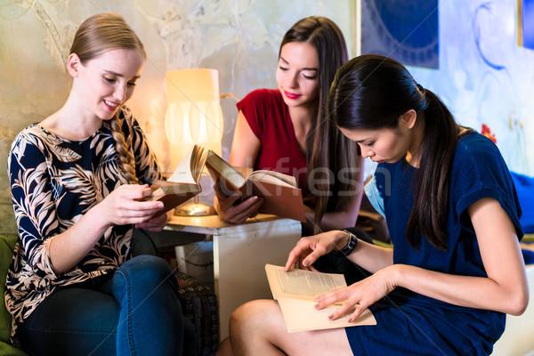 Tres las mujeres jóvenes lectura libros moderna ubicación Foto stock © Kzenon