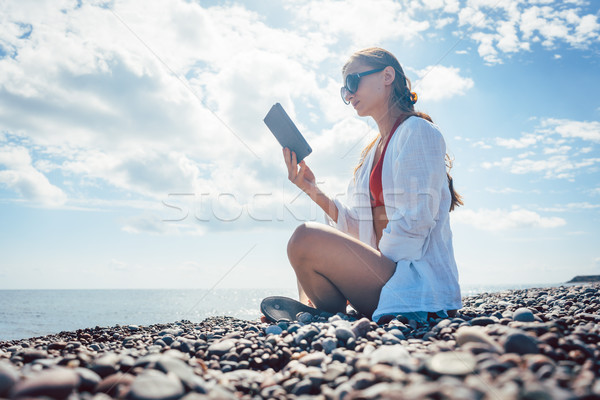 Woman reading a novel on ebook by the sea Stock photo © Kzenon