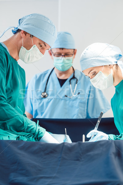 Surgical doctor in full concentration on operation Stock photo © Kzenon