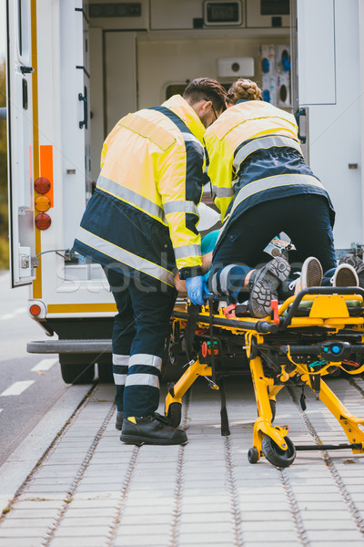 Paramedic on stretcher fighting for life of injured woman Stock photo © Kzenon