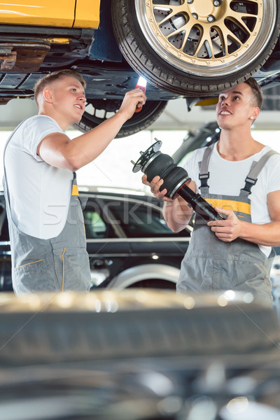 Two auto mechanics analyzing the rims of a lifted car Stock photo © Kzenon