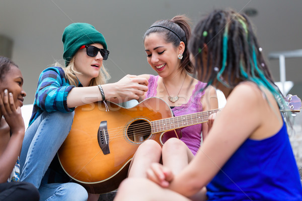 Woman teaching her friend to play guitar Stock photo © Kzenon